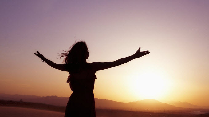 serene-young-woman-with-arms-outstretched-doing-yoga-in-the-desert-in-silhouette